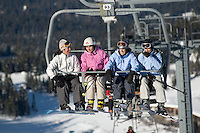 A group of women, 35-45, share a ride up the Glacier Express chairlift on Blackcomb Mountain, in Whistler, BC Canada.