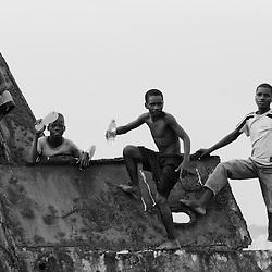 Crianças a brincarem nas praias da baía do Porto Amboim. Barco naufragado e enferrujado. Kwanza sul, Angola