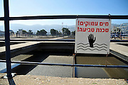 Israel, Haifa Bay Area, Sewage treatment facility. The treated water is then used for irrigation and to increase the flow n the Kishon river..Primary sedimentation pool: the sludge is allowed to settle in the pool. Sign reads: danger of drowning