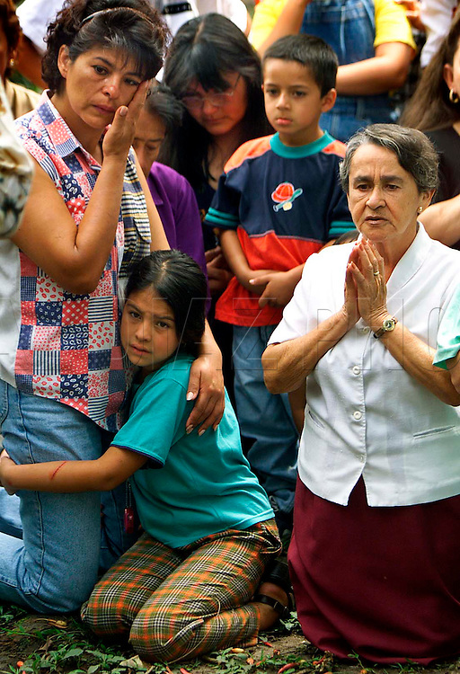 1/31/99 Al Diaz/Herald staff--Earthquake victims, Ana Rita Forero with daughter, Paola Andrea Villarreal Forero, 8, while praying with Alicia Echeveria Marti  during Catholic Mass at Bosque Park in Armenia, Colombia.<br />The Mass was held across from the Armenia fire station that collapsed during quake killing five firefighters, two civilians and destroying 15 fire and rescue trucks, ambulances and all their life saving equipment.