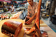 (MODEL RELEASED IMAGE). By 8:00 a.m. Giuseppe Manzo and his six co-workers have already spent an hour setting up the fish stand in Palermo, Sicily. In addition to rolling out the red tarps and unfolding the display tables, they must cut and ice the fish, devoting special attention to Sicily's beloved (and increasingly endangered) pesce spada (swordfish), freshly cut chunks of which he arranges around its severed head. Ten hours later, the crew will reverse the process, storing everything for the night. Hungry Planet: What the World Eats (p. 179).