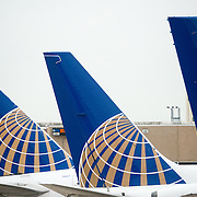 A row of three tails of United Airlines planes lined up at the gate at an airport. Each tail has the new United logo after the merger with Continental Airlines.