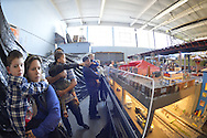 Farmingdale, New York, USA. November 26, 2016.  At Train Masters of Babylon TMB Model Train Club's Open House, visitors enjoy a 4000 square foot O Gauge model railroad with 10 trains running on 19 scale miles of track and an underground subway system. Watching O Scale model trains traveling on tracks through various elaborate scenes was family fun, free and open to the public, during the long Thanksgiving holiday weekend.