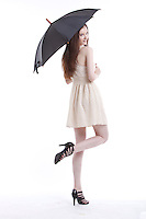 Portrait of beautiful young woman in dress with umbrella against white background