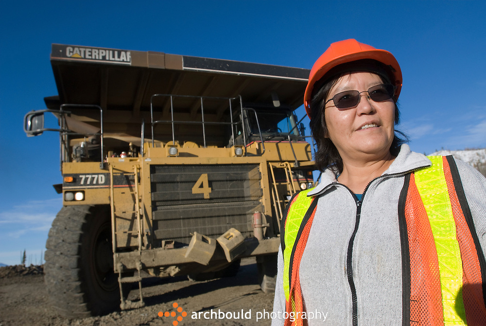 A female mining truck driver is dwarfed by her rig.