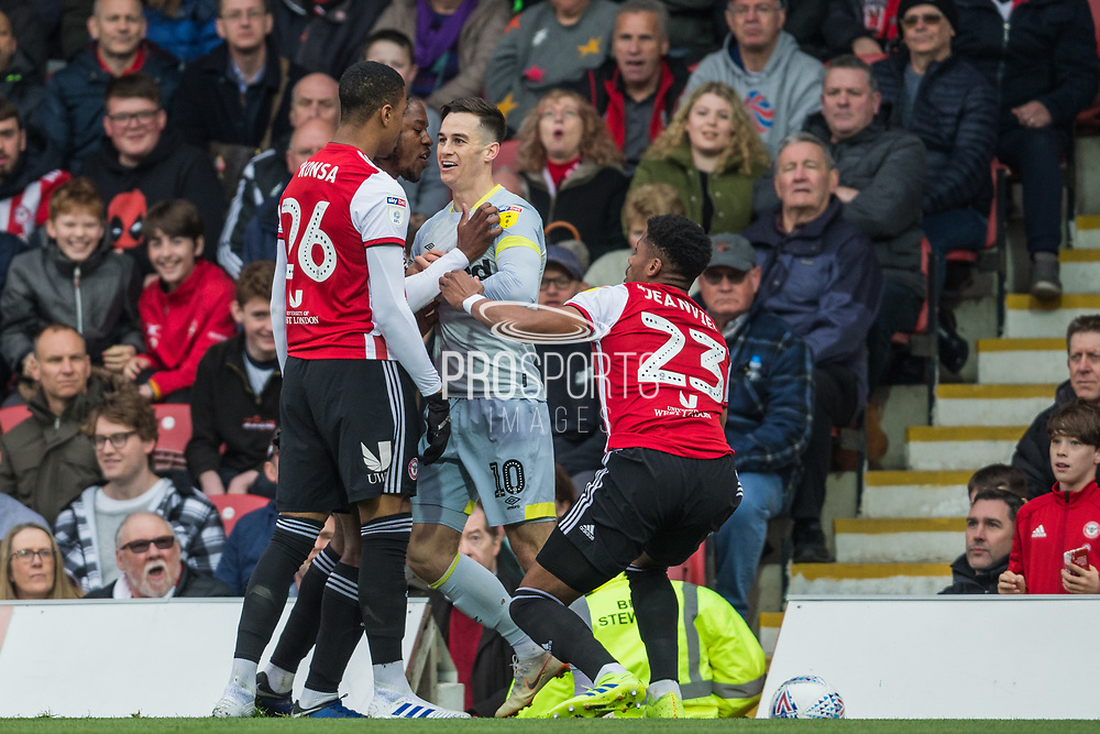 Julian Jeanvier (Brentford) now off the ground and holds back Romaine Sawyers (Capt) (Brentford) who has joined Ezri Konsa Ngoyo (Brentford) during the EFL Sky Bet Championship match between Brentford and Derby County at Griffin Park, London, England on 6 April 2019.