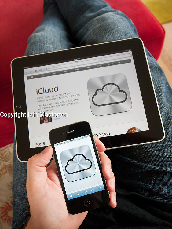 iCloud cloud computing service icon on an iPhone 4G smart phone screen with Apple website on iPad