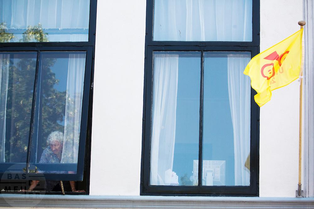 Een oudere vrouw kijkt vanuit haar woning naar de rijders. In Utrecht is deTour de France van start gegaan met een tijdrit. De stad was al vroeg vol met toeschouwers. Het is voor het eerst dat de Tour in Utrecht start.<br /> <br /> In Utrecht the Tour de France has started with a time trial. Early in the morning the city was crowded with spectators. It is the first time the Tour starts in Utrecht.