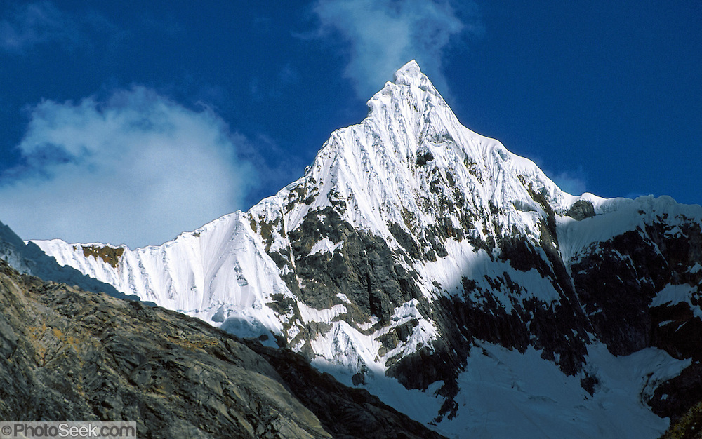 Paria peak (18,400 feet) rises sharply above the Santa Cruz Trek, in Huascaran National Park, Cordillera Blanca Mountains, Huaraz, Peru. UNESCO honored Huascaran National Park on the World Heritage List in 1985. Cordillera Blanca mountain range is in the Sierra Central of the Peruvian Andes.