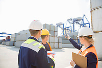 Female supervisor discussing with workers in shipping yard