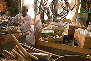 """Trader Mohammed Abdulrahman, from El Muglad (right), examines a light bulb at his hardware store in the market of Abyei. Recent developments in Abyei town are making people settle down. """"No one was thinking of using these materials before."""""""