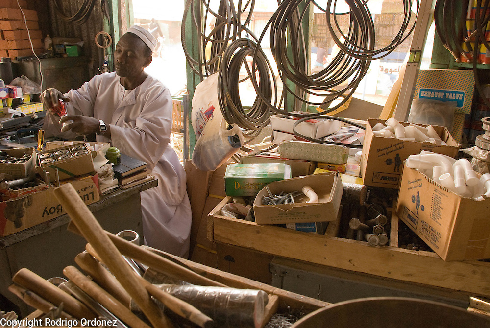 "Trader Mohammed Abdulrahman, from El Muglad (right), examines a light bulb at his hardware store in the market of Abyei. Recent developments in Abyei town are making people settle down. ""No one was thinking of using these materials before."""