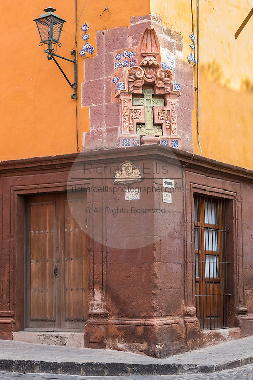 A stone cross carved into the side of a Spanish colonial adobe building in the historic center of San Miguel de Allende, Mexico.
