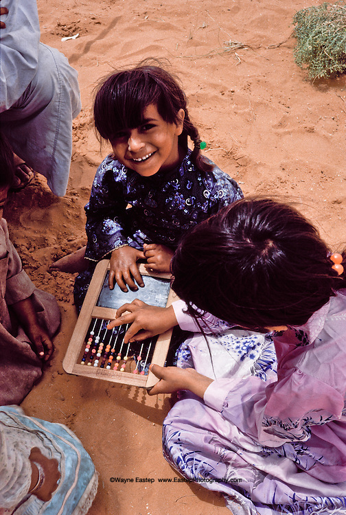 Anoud Al Amrah and friends play with counting board at Bedouin encampment in the Dahana Sands, Saudi Arabia