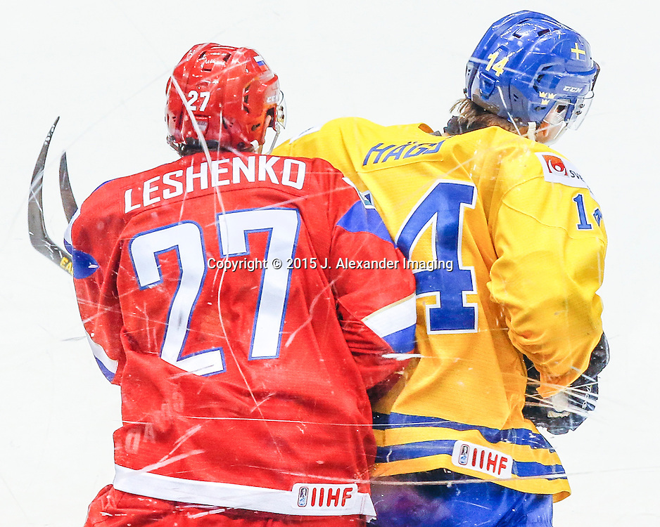 Team Russia and Team Sweden players collide near glass during the 2015 IIHF Junior World Championships.