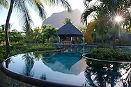 Le Morne Brabant behind an infinity pool at sunrise at the Lux Le Morne Hotel.  Le Morne Brabant Peninsula, south west Mauritius  The Indian Ocean
