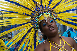 London, August 29th 2016. A woman in a yellow and blue feather head dress stares into the camera during day two of Europe's biggest street party, the Notting Hill Carnival.