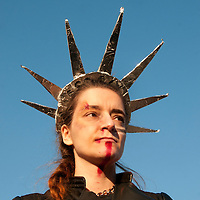 London UK. January 21st 2017.An estimated 100,000 protesters took part in a Women's March from the US Embassy in Grosvenor Square to Trafalgar Square as part of an international campaign on the first full day of Donald Trump's Presidency of the United States. A woman with a beaten up face wears a Statue of Liberty headress