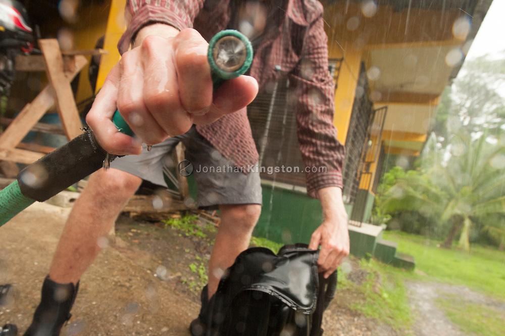 A man sprays the camera with a garden hose. (Model Released)