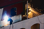 Construction workers welding and disc grinding on ship docked in the Nile River at Cairo Egypt