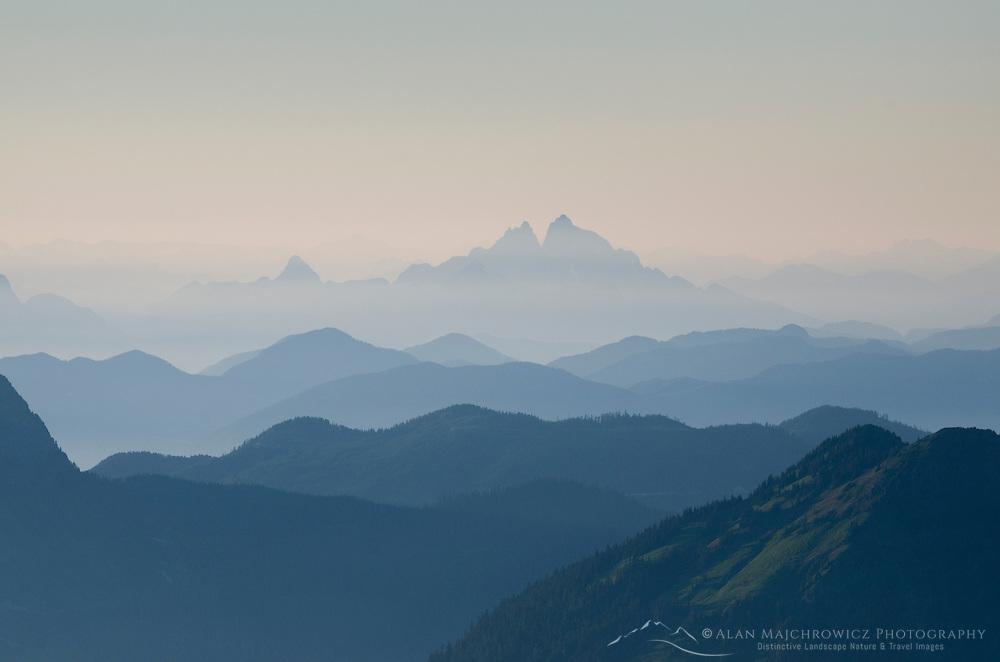 Overlapping layers of mountain ranges seen through evening haze, North Cascades Washington