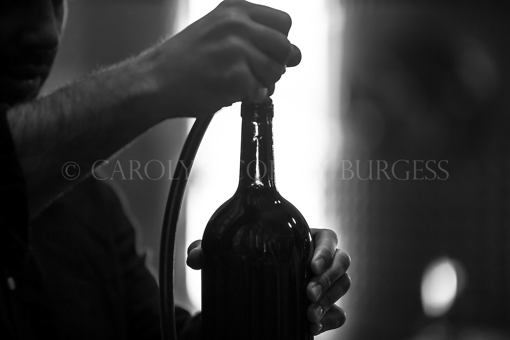 winemaker hand filling a magnum of wine