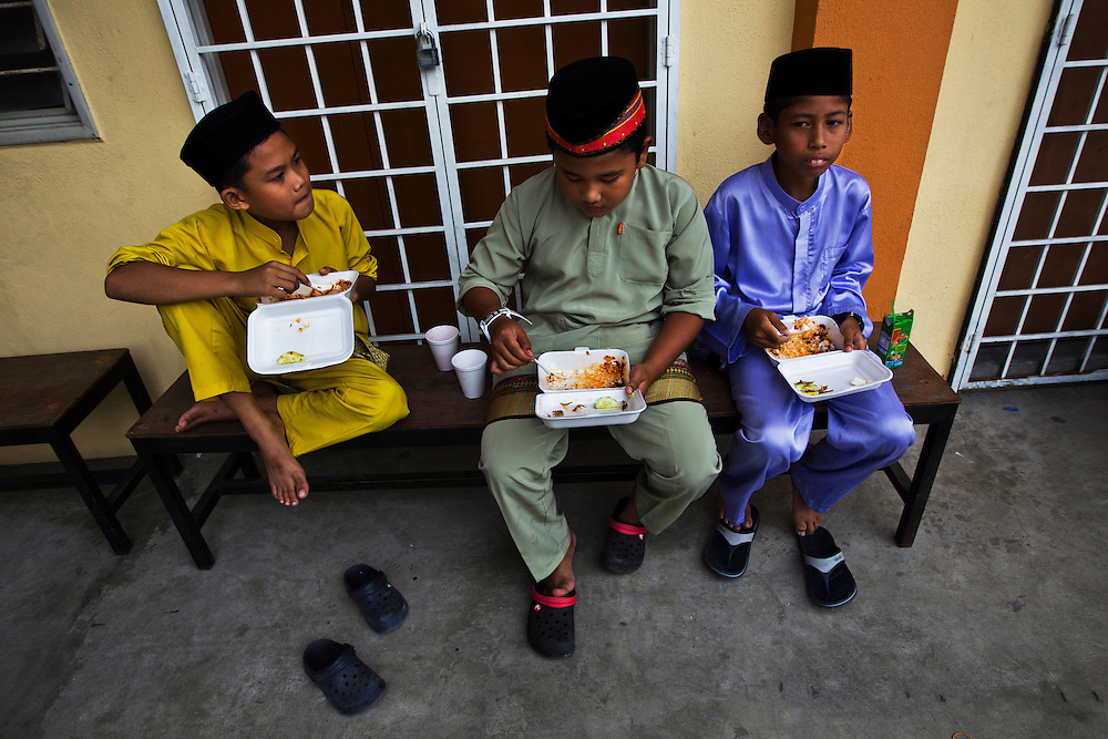 Malaysian Muslim chidren in traditional outfit having their meal during the Maulidur Rasul celebrations, Kuala Lumpur, Malaysia.