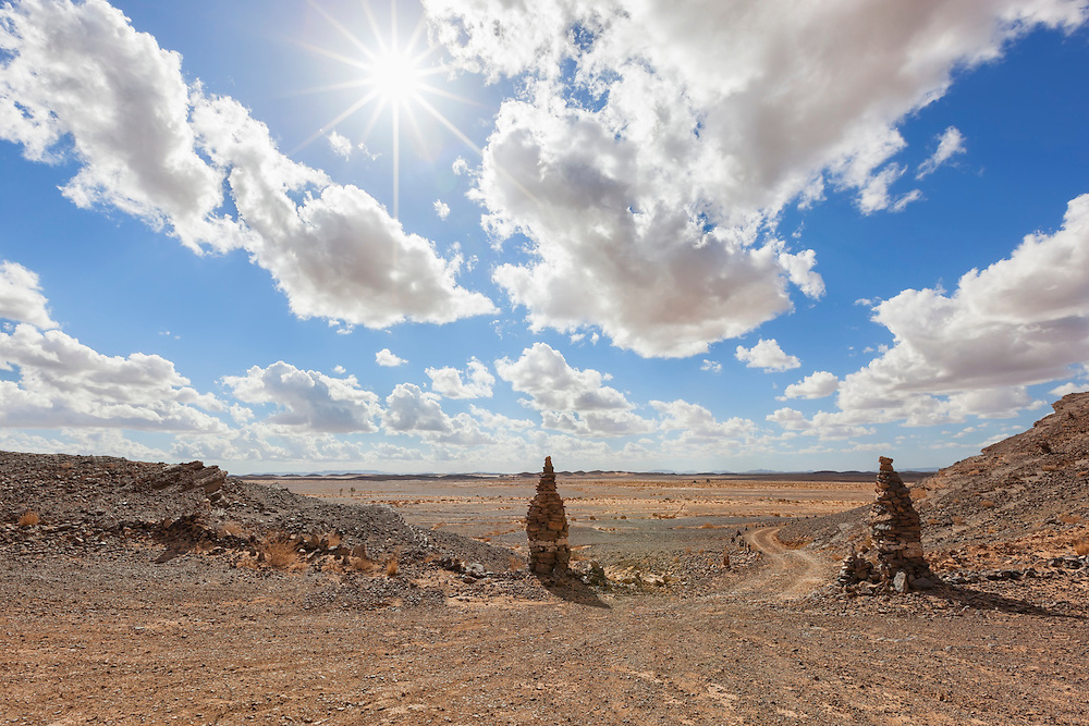 Stony desert landscape with sun and cloudy blue sky, Sahara desert, Morocco.