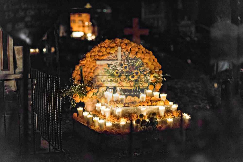 A candlelit gravesite decorated with marigolds and offerings for the Day of the Dead festival October 31, 2017 in Tzintzuntzan, Michoacan, Mexico.