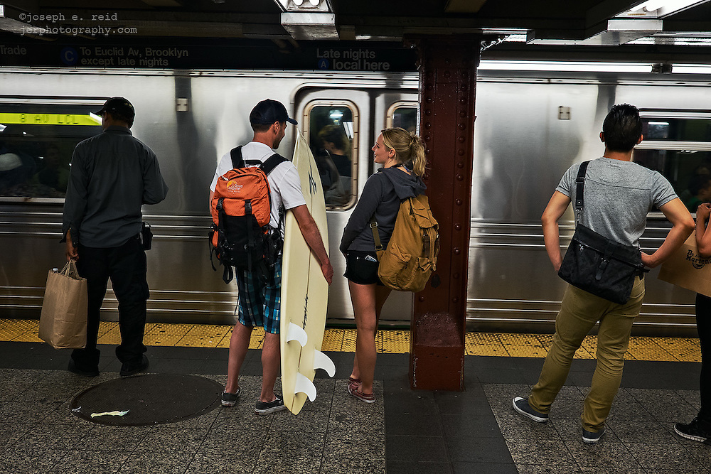 Couple with surfboard waiting for subway train, New York, NY, US