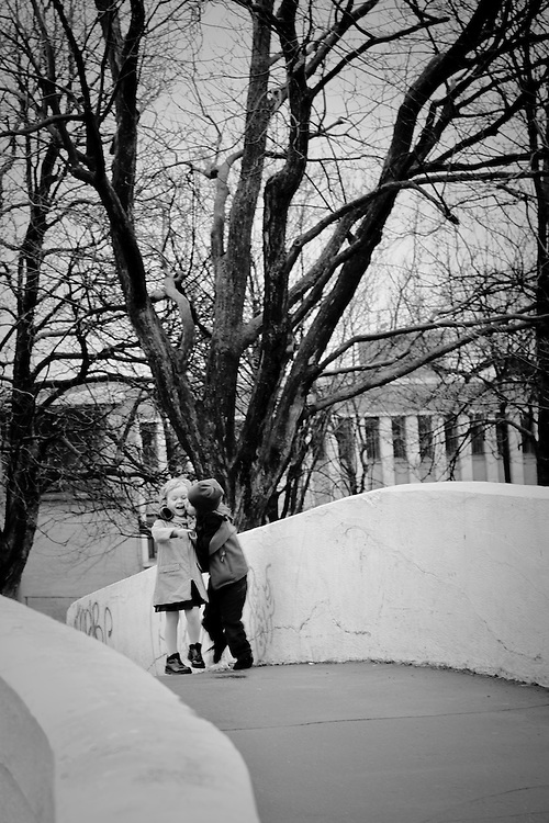 A young boy is trying to kiss a young girl a park of Outremont, Qc, Canada
