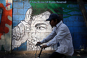 A wall wth graffiti art depicting a character unzipping his head is ignored by a passing bicyclist, in Phnom Penh, Cambodia.