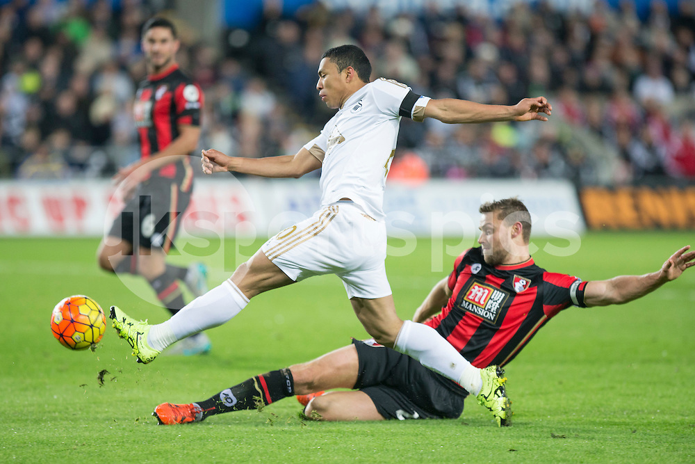 Jefferson Montero of Swansea crosses under pressure from Simon Francis of Bournemouth during the Barclays Premier League match between Swansea City and Bournemouth at the Liberty Stadium, Swansea, Wales on 21 November 2015. Photo by Mark Hawkins.
