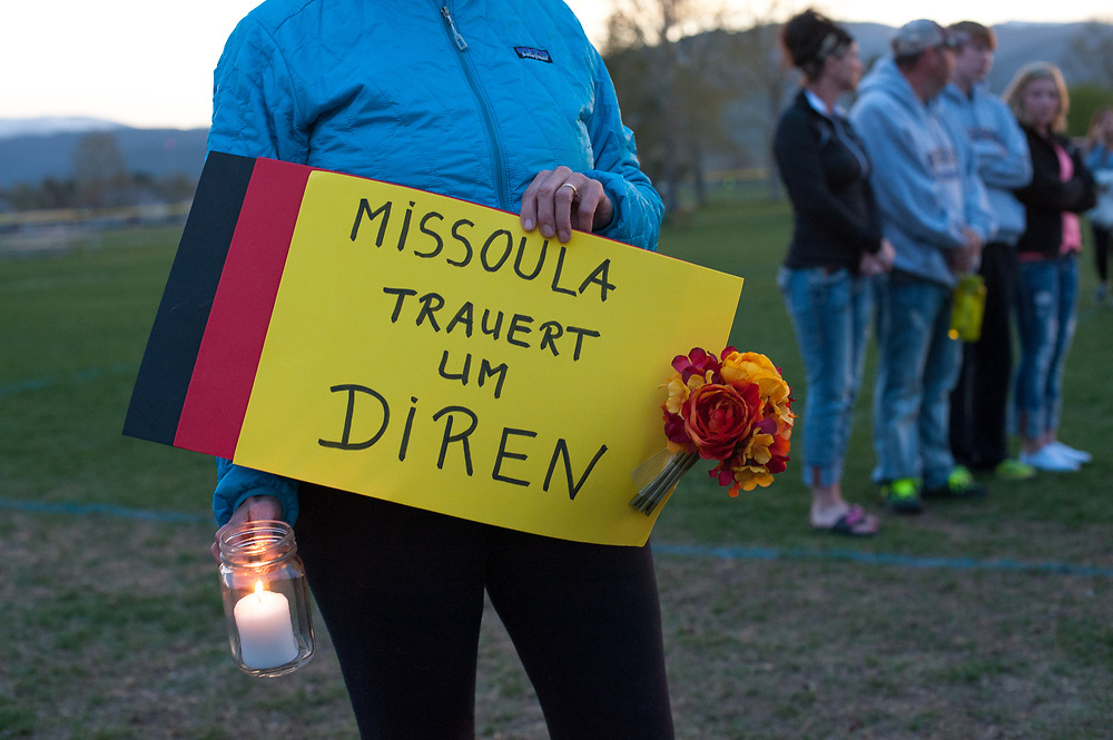 "On May 2, Urula Carpenter, a neighbor of both Diren Dede and Markus Kaarma, and a former German exchange student to the U.S., holds a sign written in German at Dede's candlight vigil that translates to mean, ""Missoula is morning for Diren."" Kaarma is accused of shooting and killing Dede in his garage on April 27, 2014."