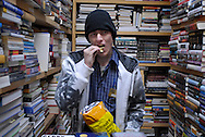 A man snacks on a bag of potato chips inside Worth a Second Look, a second hand store in Kitchener, Ontario, Canada. The man is a casual day worker at Job Cafe, a program of The Working Centre.
