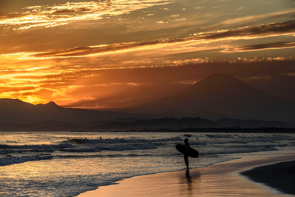 A surfer watches the sunset at Kugenuma Beach in Fujisawa City, Kanagawa Prefecture, Japan.
