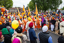 Slough, UK. 28th April 2019. The bearers of the Nishan Sahib, followed by the Pani Pyare (Five Beloved Ones), take part in the Vaisakhi Nagar Kirtan procession from the Gurdwara Sri Guru Singh Sabha to the Ramgarhia Sikh Gurdwara. Vaisakhi is the holiest day in the Sikh calendar, a harvest festival marking the creation of the community of initiated Sikhs known as the Khalsa.