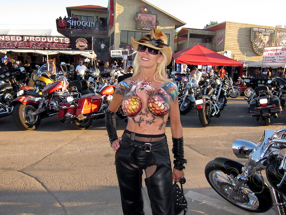 STURGIS, SOUTH DAKOTA - AUGUST 2010:  A young woman displays her body art while on Main Street in downtown Sturgis, South Dakota during the 70th annual Sturgis Motorcycle Rally held in the Black Hills.  The attendance estimates were placed between 500, 000 and 700,000 bikers.