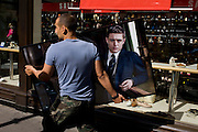 Worker carries a portrait of a male model, a fixture on its way to another premises in Soho, central London.