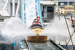 © Licensed to London News Pictures. 13/07/2019. Brighton, UK. Members of the public take a ride on the Brighton Palace Pier Big Splash water attraction as  warm weather continues to hit the seaside resort. Photo credit: Hugo Michiels/LNP