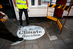 UK ENGLAND LONDON 29APR10 - Activists use a pressure washer and a stencil to do some pavement graffiti outside the Labout party office in Islington, North London. The reverse clean graffiti method uses water and a pressure washer applied to dirty surfaces to inscribe the Climate Question message onto pavements ahead of the UK general election next weekend...jre/Photo by Jiri Rezac..© Jiri Rezac 2010