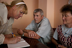 Valentia Scherbina, a paralegal, meets with Fedir Kucher, 72, and Tamara Sovenko about about their legal issues at the village community center, Bila Tserkva, Ukraine, June 14, 2011. Paralegals and attorneys meet with locals and talk about their legal issues at the village community center. More than half of the worldÕs population, four billion people, live outside the rule of law, with no effective title to property, access to courts or redress for official abuse. The Open Society Justice Initiative is involved in building capacity and developing pilot programs through the use of community-based advocates and paralegals in Sierra Leone, Ukraine and Indonesia. The pilot programs, which combine education with grassroots tools to provide concrete solutions to instances of injustice, help give poor people some measure of control over their lives.