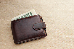 Brown leather wallet with dollar bill (Credit Image: © Image Source/Ian Nolan/Image Source/ZUMAPRESS.com)
