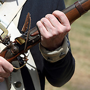 A close-up of a cocked musket rifle during a re-enactment of a United States Continental Army encampment in Jockey Hollow National Park, New Jersey, USA. The Continental Army wintered in Jockey Hollow during 1779-1782.<br />