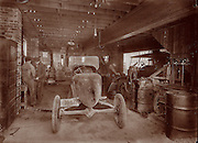 Vintage Photo: CG Schwertfeger Ford Dealer,  West Virginia. The car has 1923 WV plates. The men working on what appears to be a sports car in foreground, circa 1923 Auto mechanics working in garage.