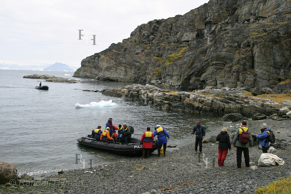 Passengers from expedition cruise ship Clipper Adventurer board rubber Zodiac raft after visiting Qilakitsoq archaeological site where eight well-preserved 15th-century Inuit mummies were rediscovered in 1972; Uummannaq, Greenland