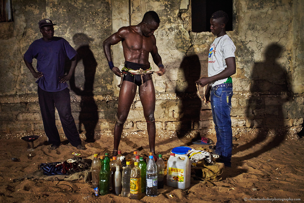 A wrestler puts numerous Gris-gris amulets onto himself before a fight in the small village Djilass on April 1, 2015.  In the foreground, one can see magic potions filled up in various bottles.