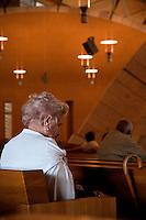 """È stata inaugurata il 1° luglio 2004, la nuova Chiesa di San Pio da Pietrelcina progettata dall'architetto Renzo Piano. Esattamente 45 anni prima, nel 1959,  veniva inaugurata la chiesa """"grande"""" di Santa Maria delle Grazie. .Sorta a fianco del santuario e convento in cui visse il frate, ha la forma di una conchiglia e la sua pianta ricorda quella della spriale archimedea. Enormi archi parto dal perimetro esterno e terminano nel fulcro della """"conchiglia"""" dove è posto l'altare. Possenti staffe d'acciaio, ancorate agli archi, sorreggono la volta che ricoperta di rame preossidato espone alla vista un intenso un colore verde-rame.   .Con i suoi 6000 mq, è la seconda chiesa più grande in Italia per dimensioni, dopo il Duomo di Milano. Può ospitare oltre 7000 persone e per la sua realizzazione sono state impiegati 30.000 metri cubi di calcestruzzo, 1.320 blocchi in pietra di Apricena, 70.000 metri cubi di scavo in roccia, 60.000 chili di acciaio, 500 mq di vetro, 19.500 mq di rame preossidato. Ogni anno è meta di oltre sei milioni di pellegrini..Nella foto, un'anziana signora è assorta in preghiera all'interno della chiesa."""