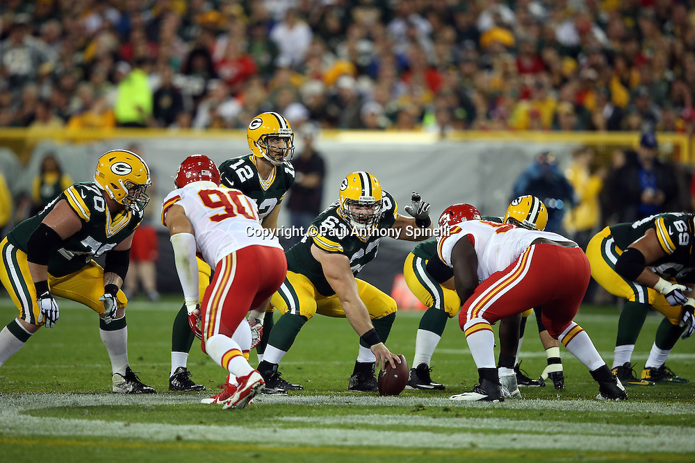 Green Bay Packers center Corey Linsley (63) waves his left arm as he gets set to snap the ball with his other hand during the 2015 NFL week 3 regular season football game against the Kansas City Chiefs on Monday, Sept. 28, 2015 in Green Bay, Wis. The Packers won the game 38-28. (©Paul Anthony Spinelli)