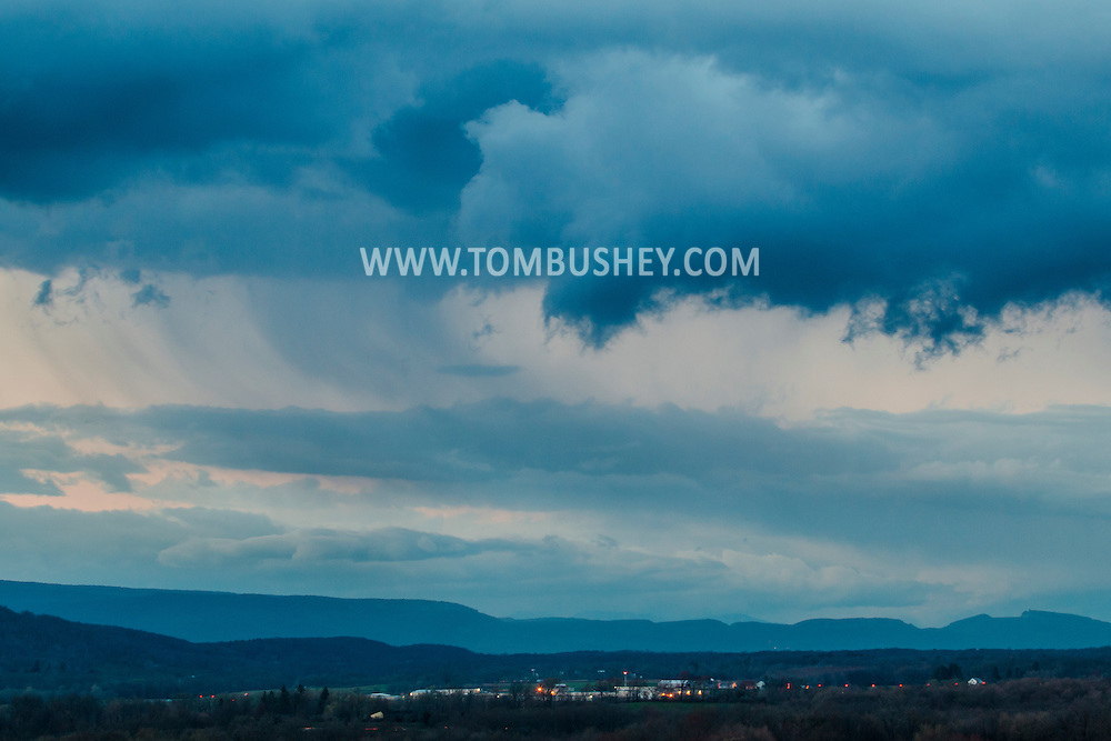 Hamptonburgh, New York - Storm clouds move over the the landscape in a view from Thomas Bull Memorial Park on Aprl 22, 2015. The lights of Orange County Airport are visible in the lower part of the frame. The Shawangunk Ridge is in the background.